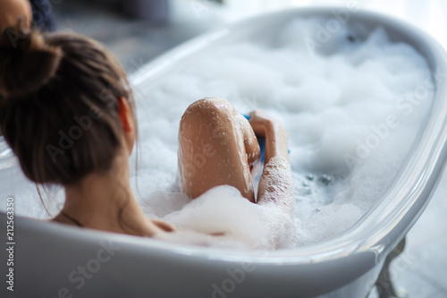 female massaging her legs with sponge in the tub. back view shot Canvas