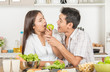 Couples are eating apple in the kitchen,and enjoy life loved