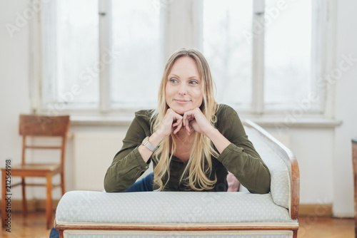 Fotografie, Obraz  Thoughtful young woman sitting on a couch