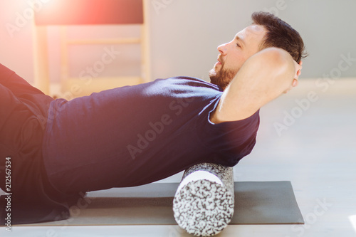 Fotografía  Handsome man performing back exercise on a foam roller being assisted at pilates studio