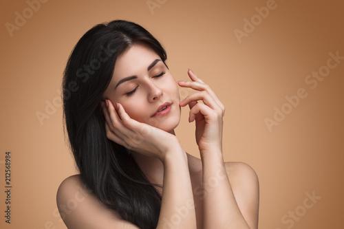 Obraz na plátně Woman touching face in studio