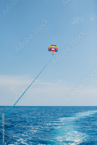 Poster Nautique motorise People flying on a colorful parachute towed by a motor boat