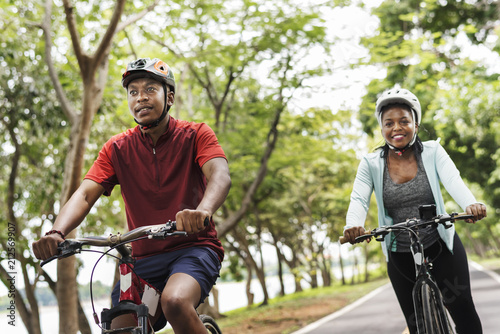 Vászonkép Cyclist couple riding together in a park