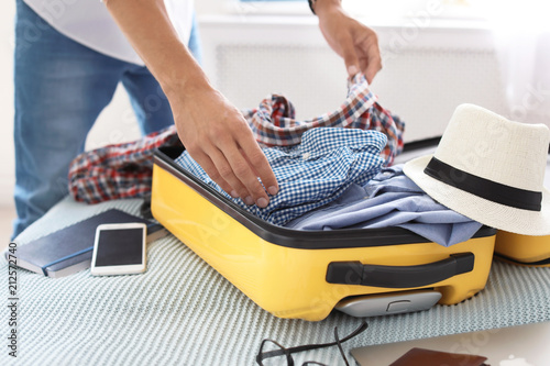 Foto Young man packing suitcase on bed, closeup