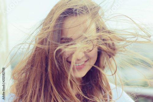 Fotografie, Obraz  Brunette beautiful disheveled hair portrait on the beach hairstyle