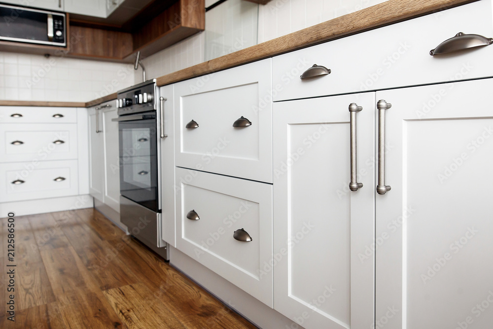Fototapety, obrazy: Stylish light gray handles on cabinets close-up, kitchen interior with modern furniture and stainless steel appliances. kitchen design in scandinavian style
