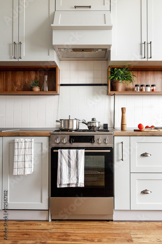 Slika na platnu Stylish gray kitchen interior with modern doors and stainless steel appliances in new home