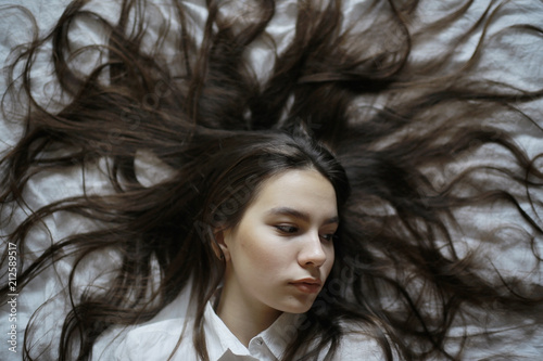 Brunette beautiful young adult with long hair lying on the bed