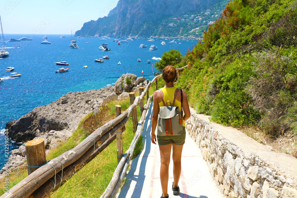 Obraz Female hiker go down and descent the pathway with spectacular landscape of Capri, Naples, Italy fototapeta, plakat