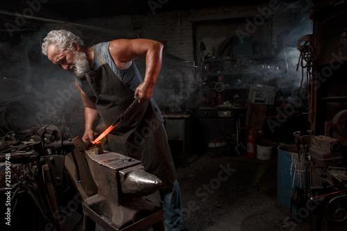 Leinwand Poster Blacksmith with brush handles the molten metal