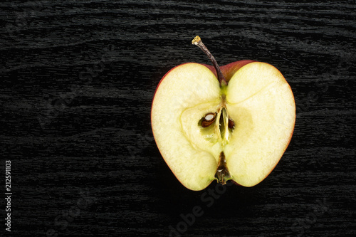 Photo  Red delicious apple one section half flatlay on black wood background