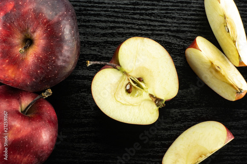Photo  Sliced red delicious apples flatlay on black wood background two whole one half and three slices