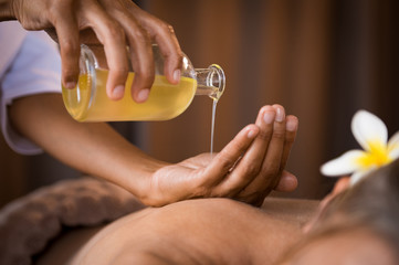 Therapist pouring massage o...