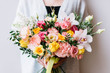 Very nice young woman holding beautiful fresh blossoming bouquet of orchids, narcissus, roses, carnations, eustoma in pink and yellow colors on the grey background