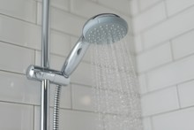 Close-up Of Chrome Shower, Faucet, In The Bathroom Covered Decorative Ceramic Tiles With White Glossy Bricks. Water Running From Shower Head