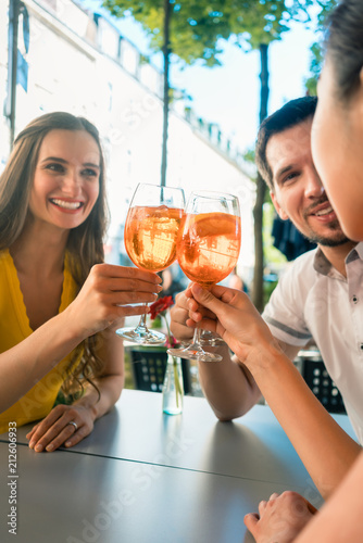 Beautiful woman and her best friends toasting with a refreshing alcoholic drink Fototapete