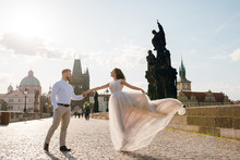 Beautiful Happy Wedding Couple Of Groom And Bride In Gorgeous Dress Dancing And Smiling While Walking On The Charles Bridge I The Evening On Sunset. Prague, Czech Republic