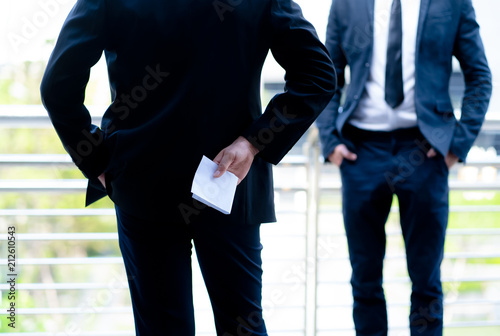 Fototapeta Businessman holding money in white envelope behind his back conceptual of, bribe, graft or corruption, cropped closeup the bribe the concept of corruption and anti bribery obraz