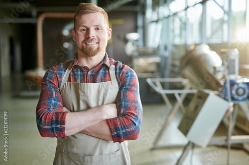 Waist up portrait of smiling bearded man wearing apron posing standing confident Wallpaper Mural