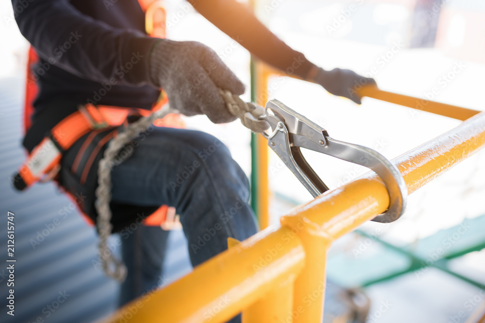 Fototapeta Construction worker wearing safety harness and safety line working at high place