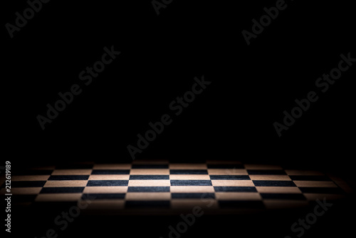 Photo abstract chessboard on dark background lighted with snoot