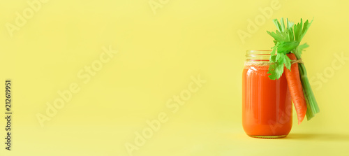 Banner of carrot juice with carrots, celery on yellow background. Vegetable smothie in glass jar. Copy space. Summer food concept. Healthy detox eating, alkaline diet