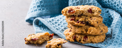 Oat meal cookies with raisins and cranberries on light gray background and blue napkin. Health breakfast or snack concept. Banner.