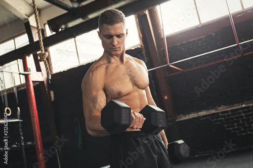 Deurstickers Wanddecoratie met eigen foto Young handsome bodybuilder during his arm workout in the gym