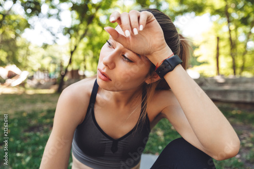 Fotomural Close up of a tired young fitness girl wiping her forehead
