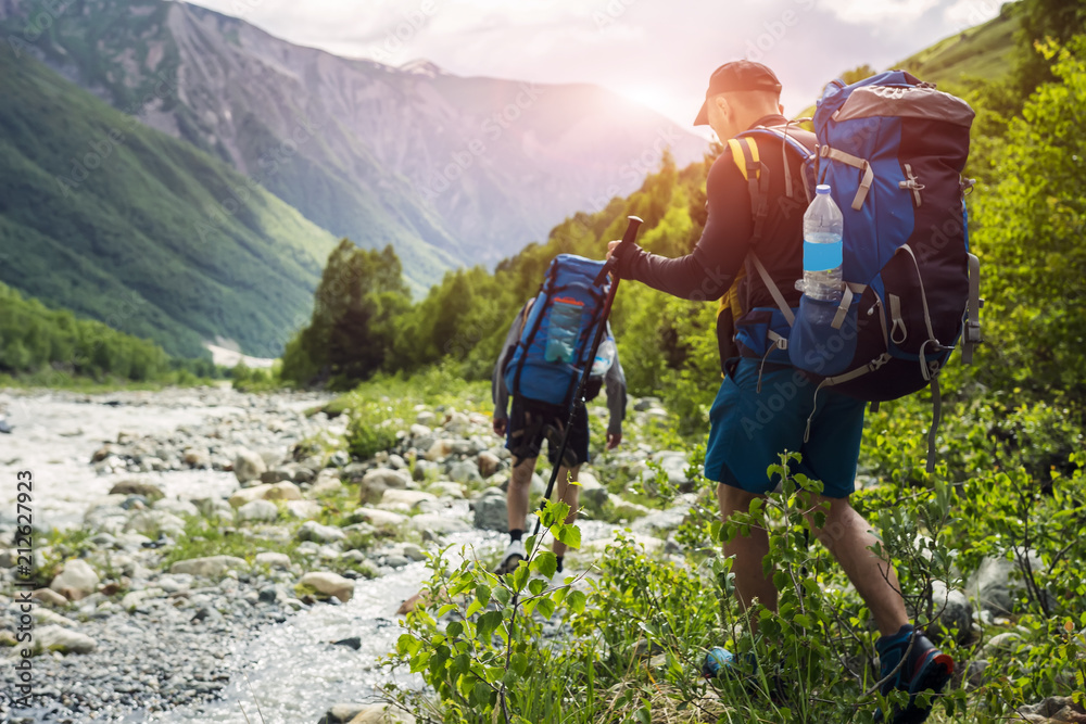 Fototapety, obrazy: Tourists with hiking backpacks on beautiful mountain landscape background. Climbers hike to mounts. Group of hikers walking in mountains