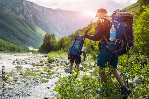 Tourists with hiking backpacks on beautiful mountain landscape background. Climbers hike to mounts. Group of hikers walking in mountains