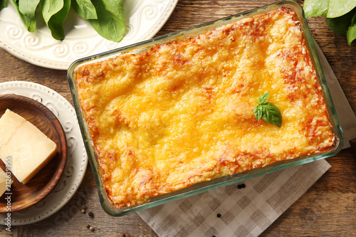 Baking tray with spinach lasagna on wooden table