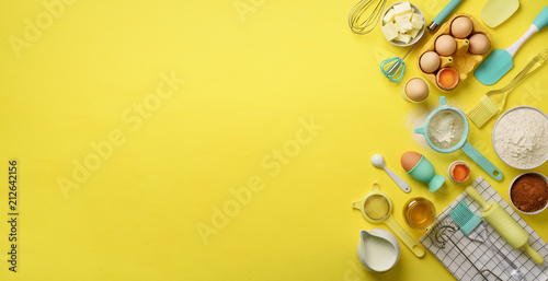 Fotografía  Banner of baking ingredients - butter, sugar, flour, eggs, oil, spoon, rolling pin, brush, whisk, towel over yellow background