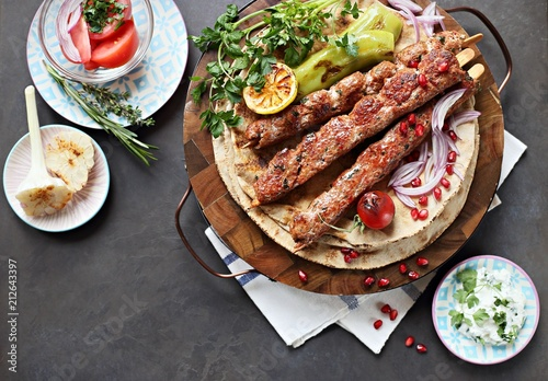 Kebab. Traditional middle eastern, arabic or mediterranean  meat kebab with vegetables and herbs. Overhead view, copy space