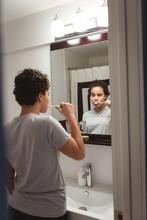 Woman Brushing Off Her Teeth In Washroom