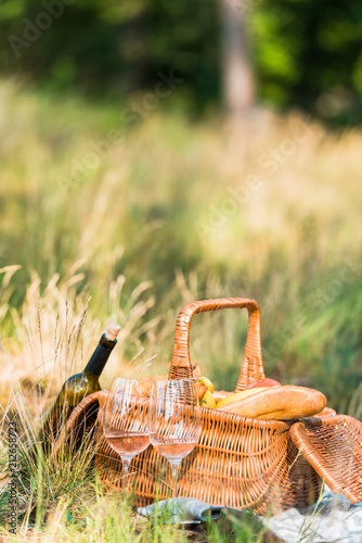 wine bottle, glasses and basket with loaves on grass at picnic Fototapeta
