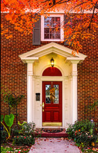 Entrance To Brick House With Pillars For Porch And Red Door With Autum Leaves On Sidewalk And Colorful Branches Framing Picture - Fall Flowers On Leaded Glass Window In Door