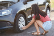 Horizontal view of experienced female driver tries to fix flat tire, uses special equipment, solves problem with wheel, poses on road side, can`t continue driving, has damaged wheel, changes rubber
