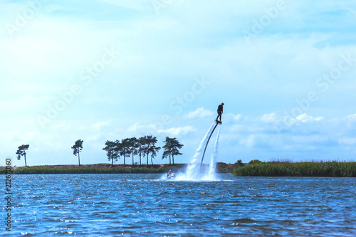 Poster Nautique motorise a man is riding a flyboard on a lake on a sunny day, toned