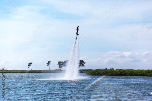 Poster Nautique motorise a man is riding a flyboard on a lake on a sunny day