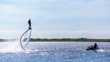 A Man Is Riding A Flyboard On A Lake On A Sunny Day
