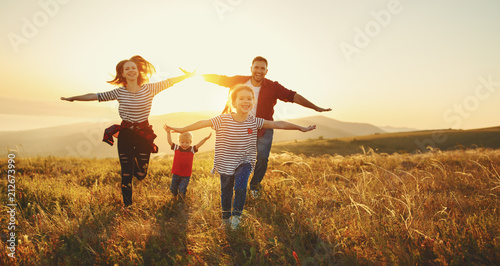 Happy family: mother, father, children son and daughter on sunset