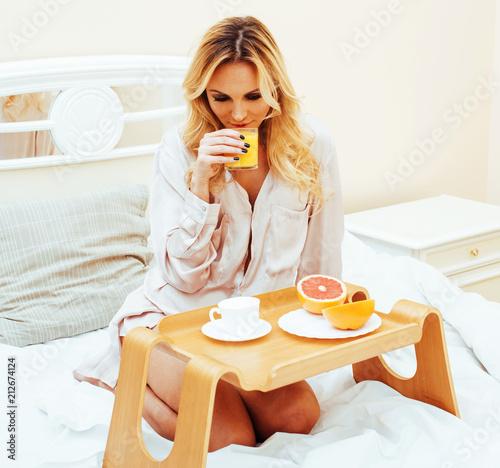 Tuinposter Kruidenierswinkel young beauty blond woman having breakfast in bed early sunny mor
