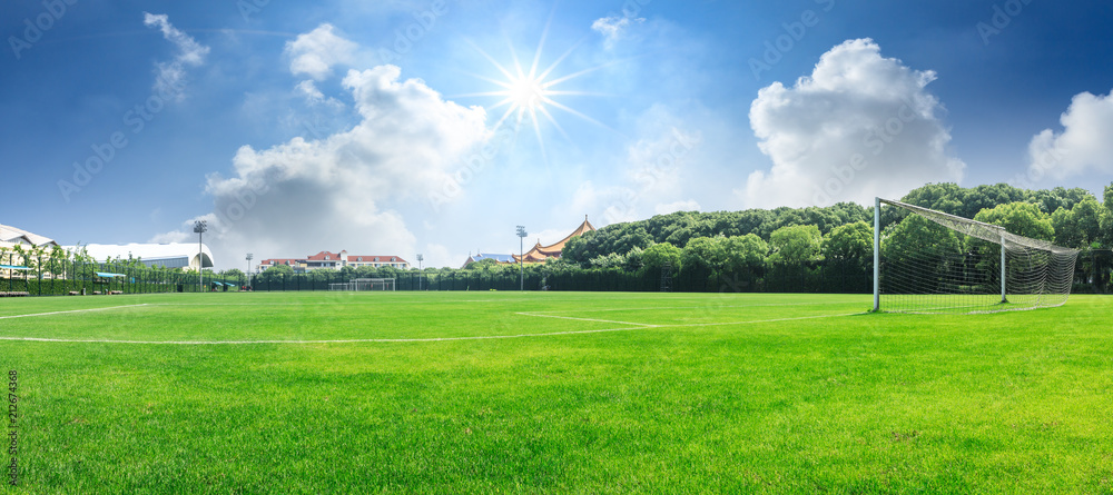 Fototapeta Green football field under blue sky background