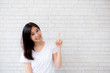 Portrait of beautiful asian woman happiness standing finger pointing something on gray cement texture grunge wall brick background, businesswoman is a smiling on concrete, business people concept.