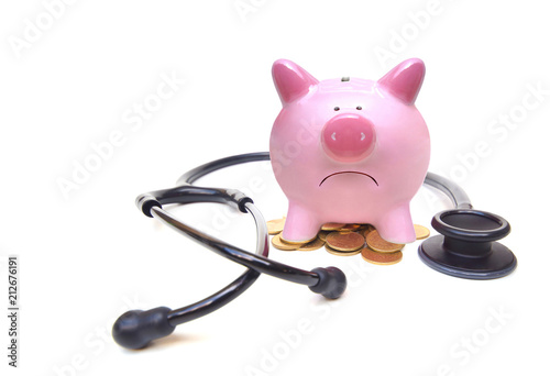 A sad pink piggy on a small pile of golden coins with a stethoscope isolated Poster