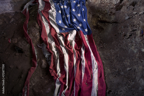 Fotografía  Symbolic Tattered and Torn American Flag on the Ground in Dirt