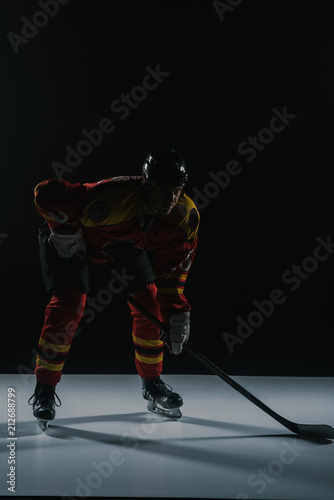 full length view of sportsman in protective sportswear playing ice hockey on bla Canvas Print