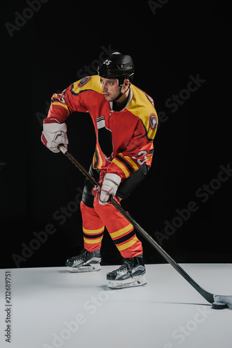 full length view of professional sportsman playing hockey and looking away on bl Canvas Print