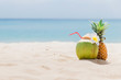 Fresh young coconut and pineapple lying on the sand beach background with straw ready for drink. Tropical vacation travel concept